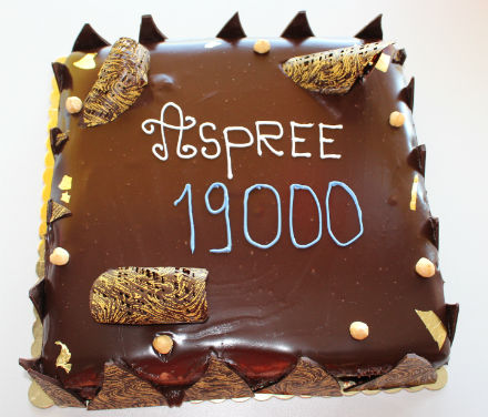 A chocolate cake with ASPREE 19000 written in blue and white icing on top.