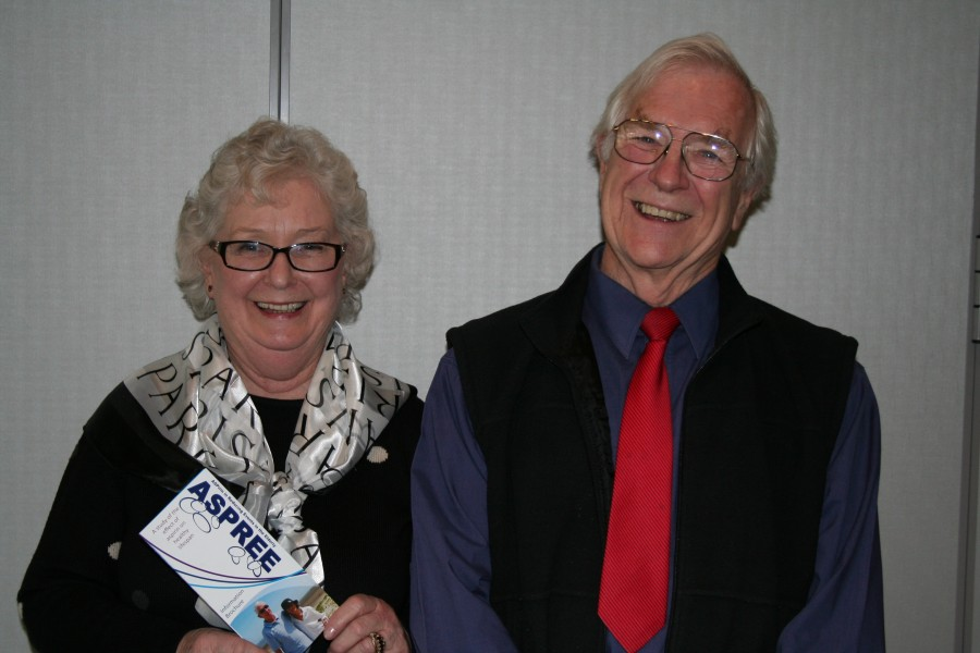 Older lady with black rimmed glasses holds an ASPREE brochure, next to an older gentleman wearing a red tie and blue shirt.
