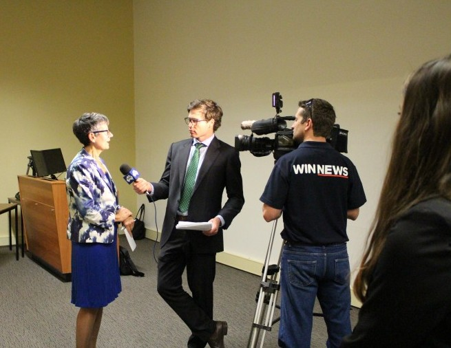 A woman is interviewed by a TV news crew