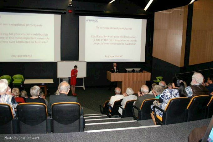 Older adults site in the lecture theatre listening to a suited man standing behind a lectern thank them for participating in the ASPREE trial.