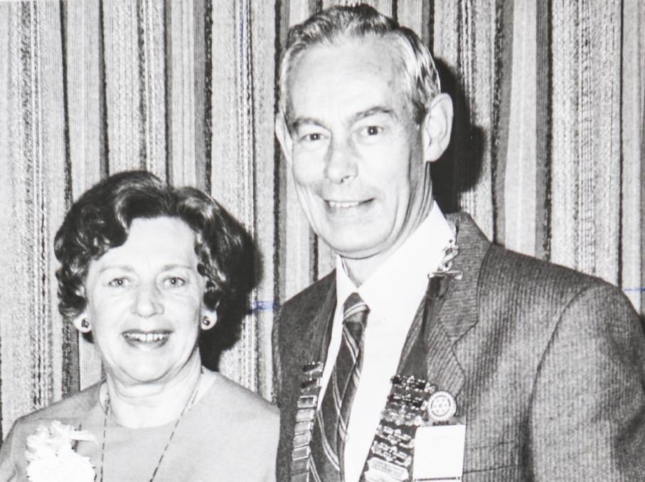 Black and white photo of a man and woman standing together. The man has several badges on his suit jacket.
