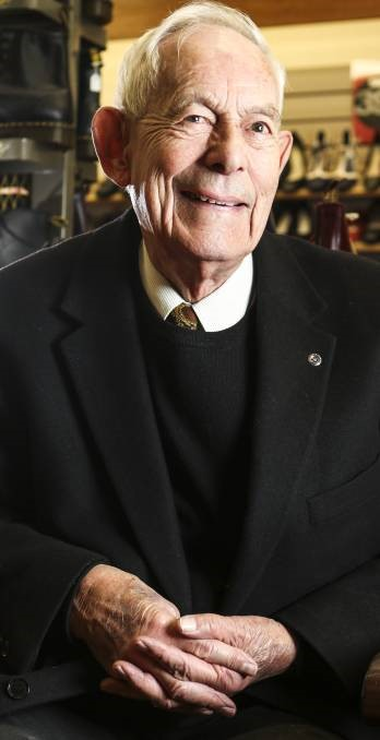 An older man in a dark suit sits with his hands together