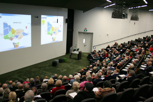Inside a large lecture theatre, with a map of ASPREE sites projected onto the wall