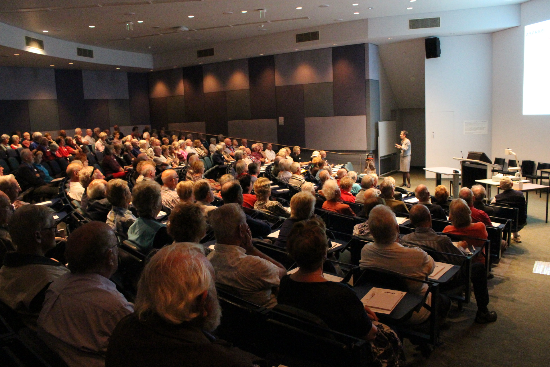 Older adults fill a lecture theatre, listening to a suited woman explain aspects of the ASPREE trial displayed on the large screen behind her