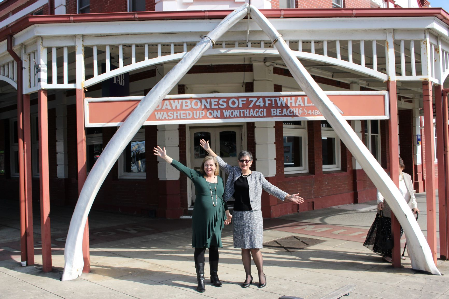 Two women stand under the Jawbones of the 74ft whale at Wonthaggi