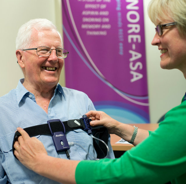 An older gentleman in a blue shirt has the SNORE-ASA  portable sleep apnoea device placed across his chest by a researcher