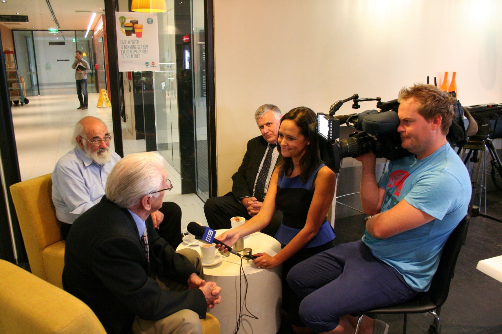 Older grey haired gent being interviewed by a news crew inside a cafe.