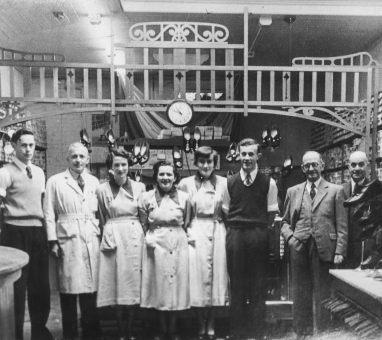 A black and white photograph of men and women with shelves of shoes and a clock face behind them