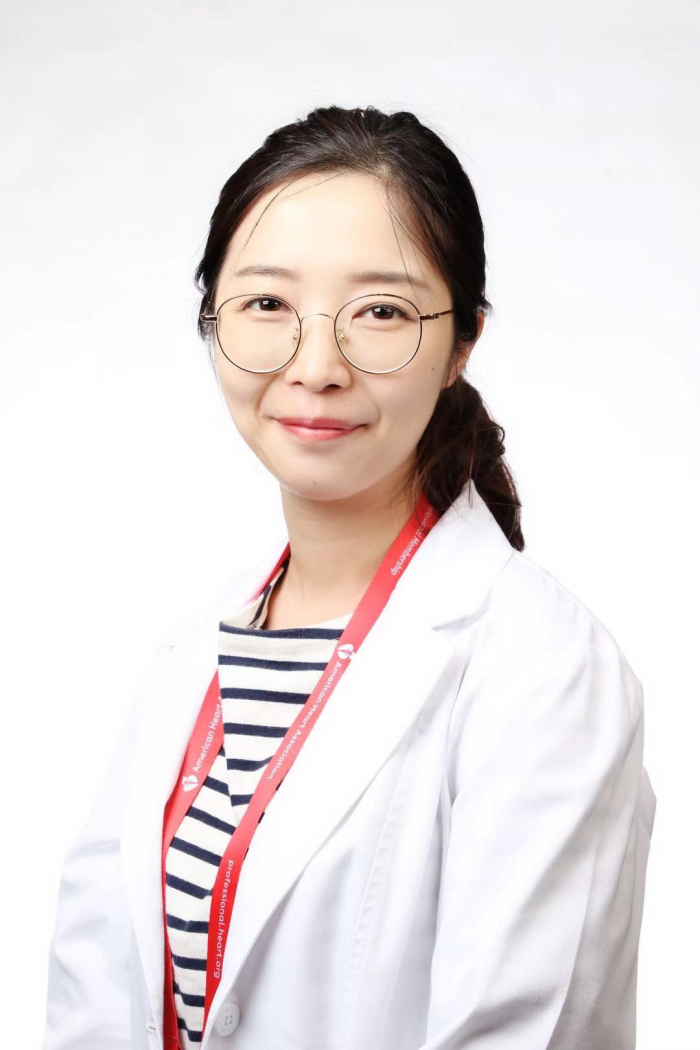 Woman with dark hair, glasses in a white coat, in front of a white background, smiles at the camera